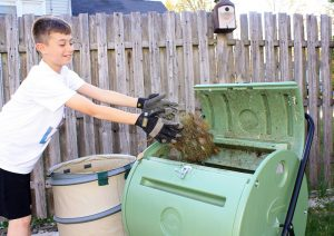 kids_composting_adding_grass_clippings